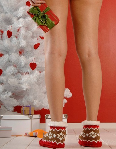 Woman´s legs wearing knit socks, holding a Christmas present in front of the Christmas tree : Stock Photo