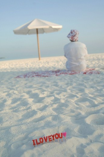 Stock Photo: 1848R-348389 I love you: love declaration and man sitting on the beach, Diffushi Island, Holiday Island, Southern Ari Atoll, Maldives, Indian Ocean