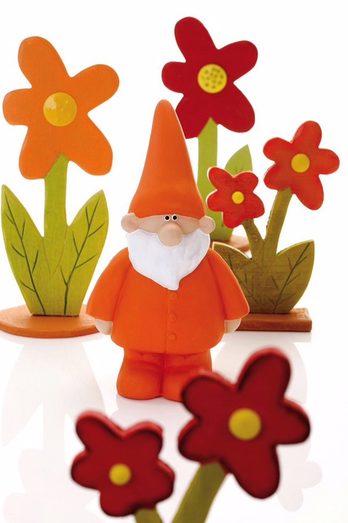 Orange garden gnome standing in the middle of colored wooden flowers : Stock Photo
