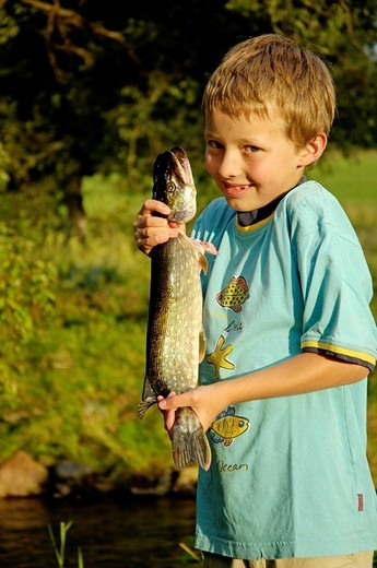 Boy, nine-year-old, is proudly holding a fish pike that he caught himself : Stock Photo