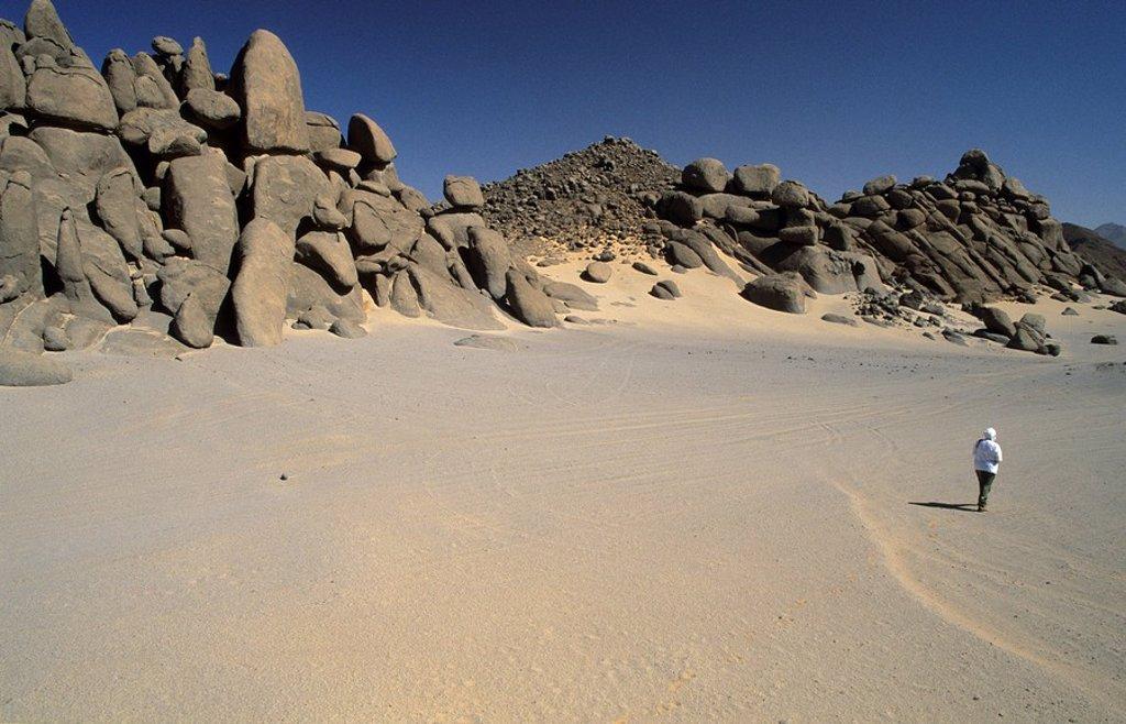 Man walking in a valley of Jebel Uweinat, Jabal al Awaynat : Stock Photo