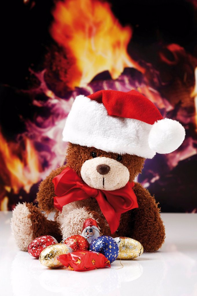 Stock Photo: 1848R-349646 Teddybear with Christmas hat, chimney fire at back