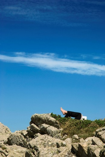 Man reading, stretching his feet towards the sky, relaxing : Stock Photo