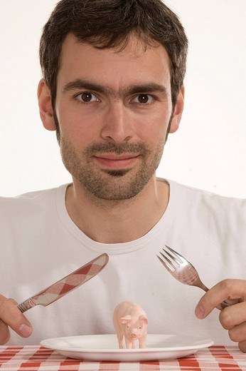 Man holding cutlery over a pig on a plate, nutrition, genetically modified food : Stock Photo