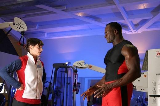 Personal trainer coaching young woman with cable machine at a gym : Stock Photo