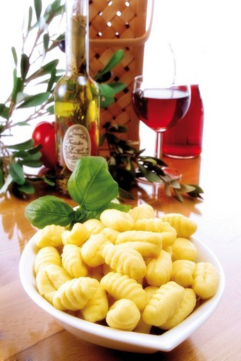 Stock Photo: 1848R-351482 Italian ambiance: gnocchi with basil, red wine, olives and an olive twig