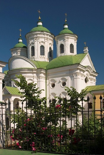 Stock Photo: 1848R-352370 Ukraine Kiev district Podil Pokrovs´ka cerkva church of Marias protection 1766-1772 roses and flowers at the wall green roofs of the church blue sky 2004