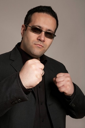 Businessman wearing sunglasses ready for a fight : Stock Photo