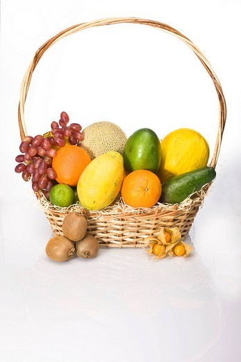 Exotic fruit in a basket, melons, grapes, oranges, lime, physalis, kiwis, mango, papaya, avocado : Stock Photo