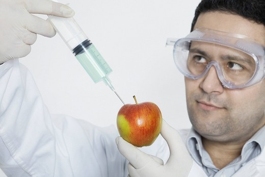 Chemist injecting substance into an apple : Stock Photo