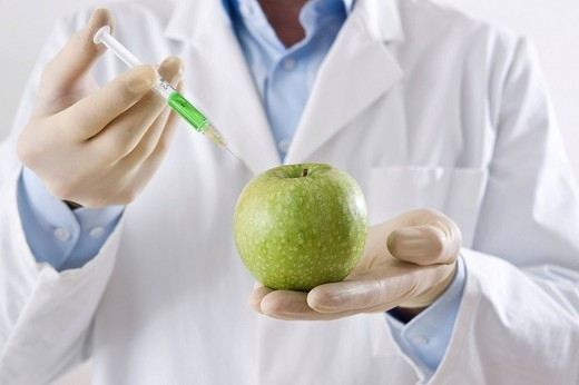 Man in a laboratory injecting liquid into an apple : Stock Photo
