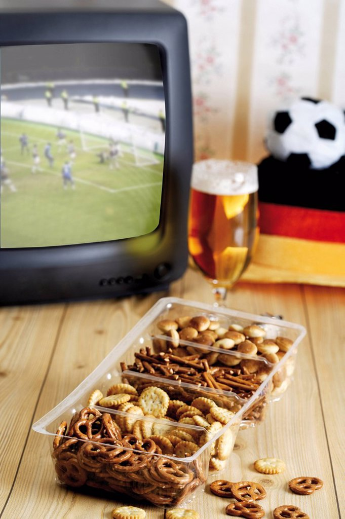 Retro football broadcast - TV broadcast of a game, football hat, glass of beer and a tray of crackers : Stock Photo