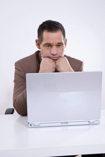 Businessman sitting in front of his laptop, lost in thought : Stock Photo