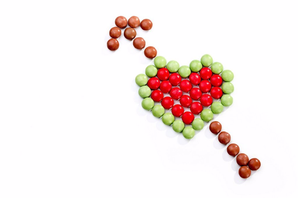 Stock Photo: 1848R-360219 Heart shape with an arrow made of coloured chocolate drops