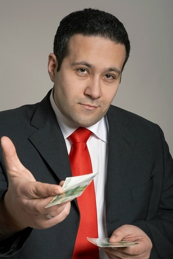 Stock Photo: 1848R-360876 Businessman offering 100-Euro bill toward camera