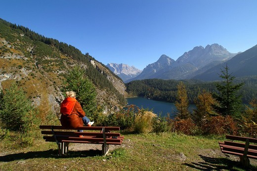 Stock Photo: 1848R-362707 Woman sitting on a bench, Blindsee, view to Zugspitze, Sonnenspitze and Schartenkopf, Tyrol, Austria