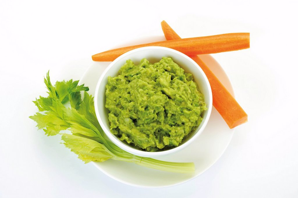 Nachos and avocado dip guacamole garnished with carrots and celery : Stock Photo