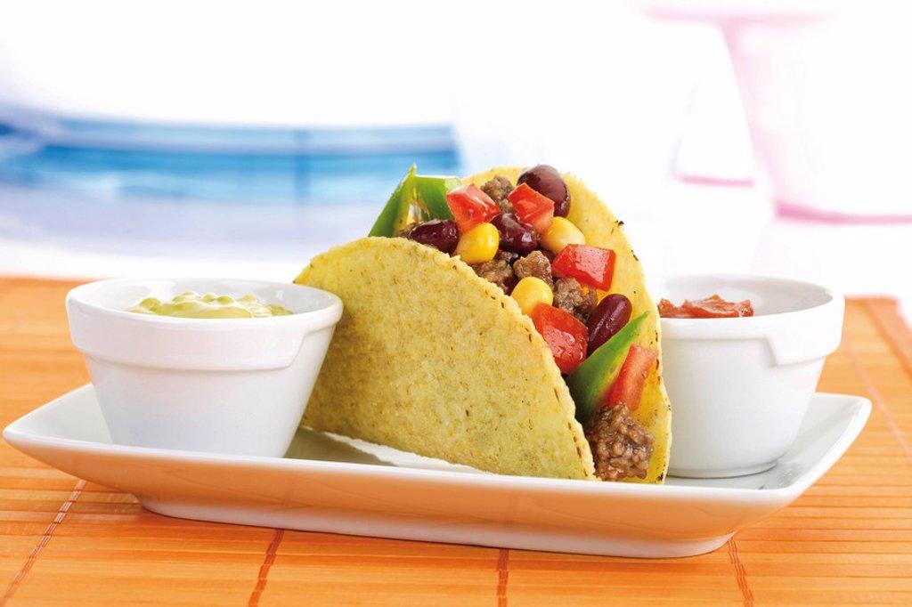 Taco shell with chili con carne, guacamole and tomato salsa : Stock Photo
