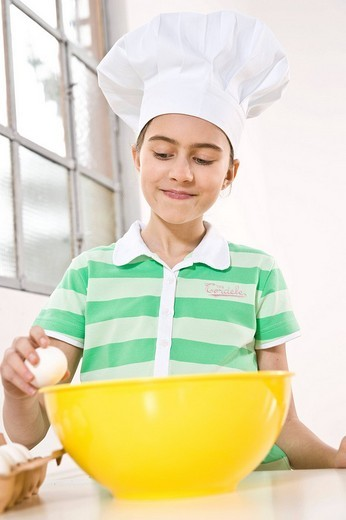 Girl wearing a chef´s hat cracking an egg into a bowl : Stock Photo