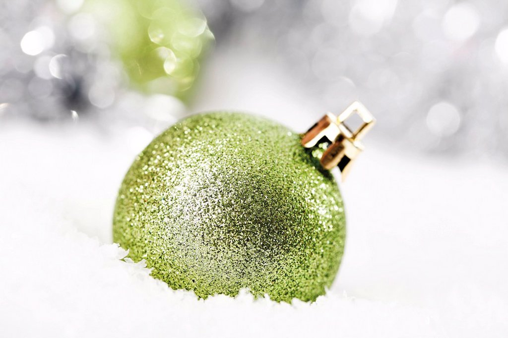 Green glitter Christmas tree ball on snow with Christmas decorations : Stock Photo