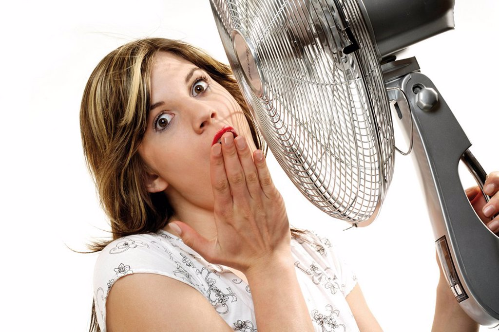 Young woman cooling off in front of a fan : Stock Photo