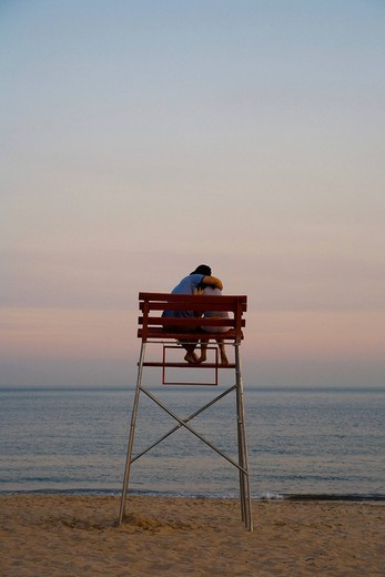 Stock Photo: 1848R-368989 Loving couple sits in a lifeguards chair at sunset