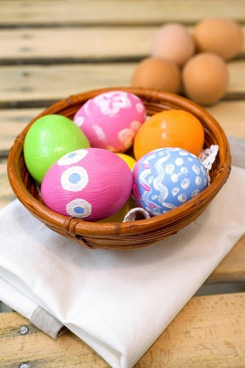Hand-painted Easter eggs in a brown bamboo bowl : Stock Photo