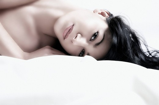 Young dark_haired woman lying and looking at the viewer, portrait : Stock Photo