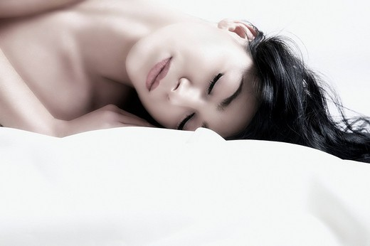 Young dark_haired woman lying with eyes closed, portrait : Stock Photo