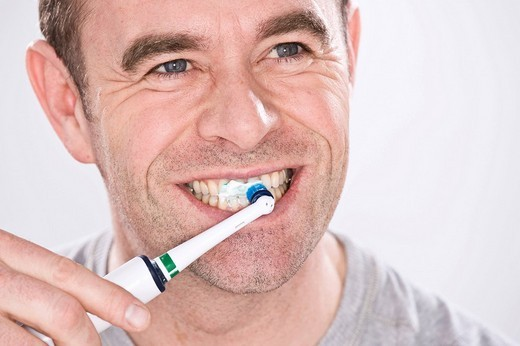 Man cleaning his teeth with an electric toothbrush : Stock Photo