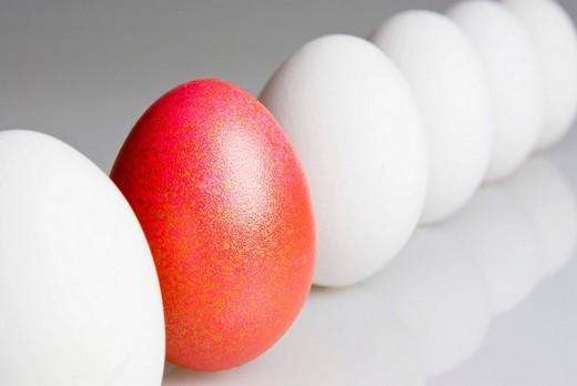 Stock Photo: 1848R-373487 Single red egg in a row of white eggs