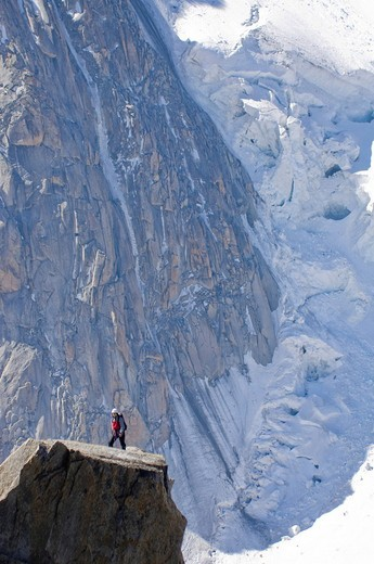 Mountain climber standing on a rock platform in front of the edge of a glacier on Mont Blanc, Chamonix, France : Stock Photo