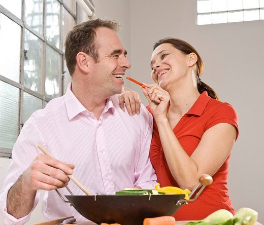 Stock Photo: 1848R-376873 Man and woman cooking vegetables in a wok