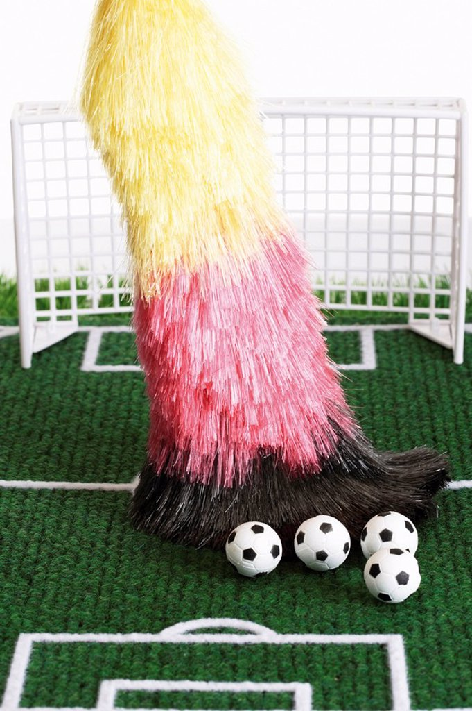 Stock Photo: 1848R-377557 End of the season: broom with German national colours sweeping footballs from the football pitch
