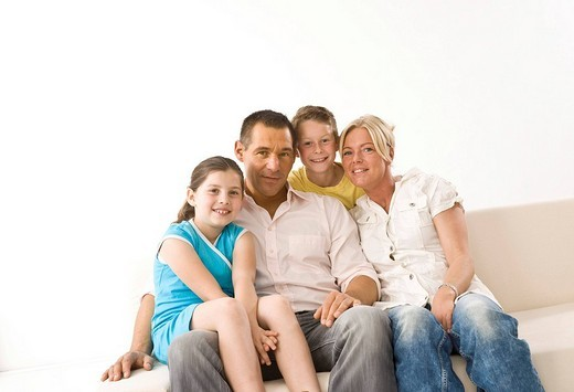 Laughing family sitting on a couch : Stock Photo