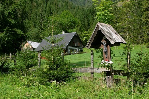 Stock Photo: 1848R-379390 Old wooden house and a wooden cross in the foreground in the village of Hinterwildalpen in the mountain region Gesäuse Styria Austria