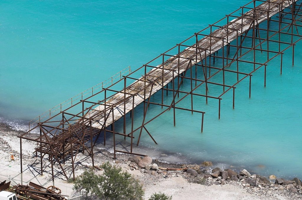 Stock Photo: 1848R-379414 Discarded supply chain, turquoise sea due to pumice sedimentation on the seafloor  Pumice and obsidian are mining at Lipari since historical times  White as snow, a weird view under the hot summer sun