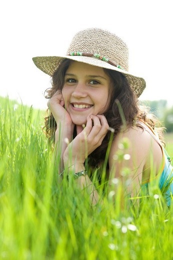 Portrait of a smiling girl wearing a sun hat while lying on a meadow : Stock Photo