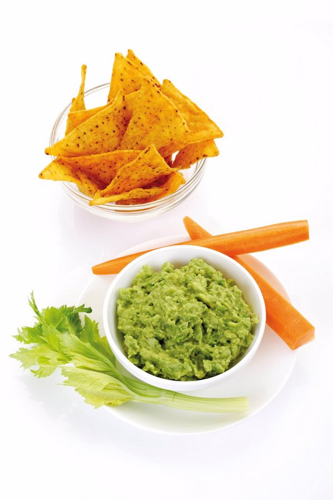 Stock Photo: 1848R-381570 Nachos and avocado dip guacamole garnished with carrots and celery