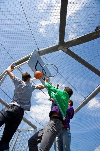 Three boys playing basketball : Stock Photo