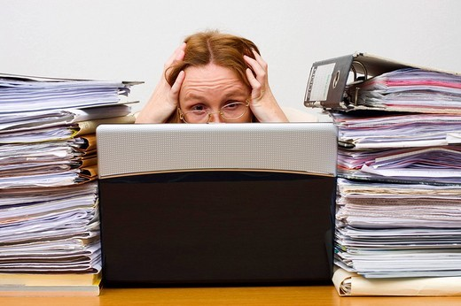 Overworked businesswoman, 41 years, with notebook and piles of documents : Stock Photo