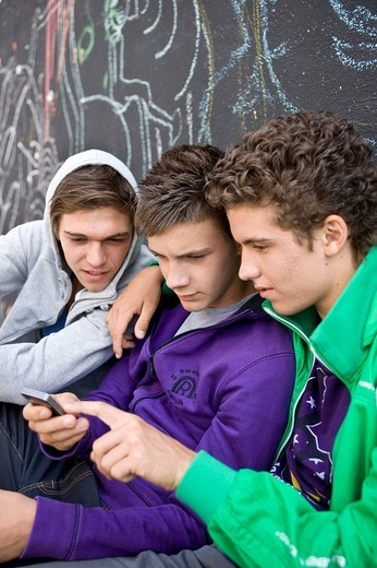 Three boys sitting in front of a wall, sending a text message : Stock Photo