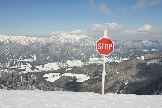 Stop sign and in the background the mountain Schneeberg ski area Stuhleck Styria Austria : Stock Photo