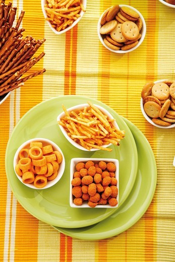 Stock Photo: 1848R-385991 Various spiced snacks in bowls, crisps, potato sticks, roasted peanuts, pretzel sticks and potato rings