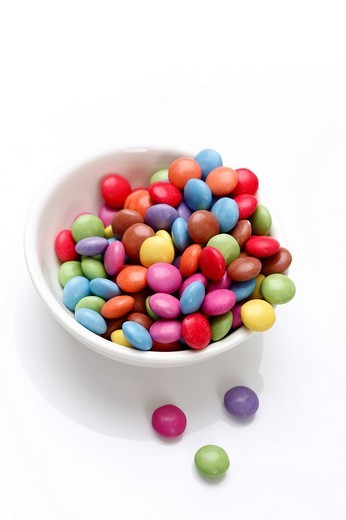 Coloured chocolate drops in a white bowl : Stock Photo