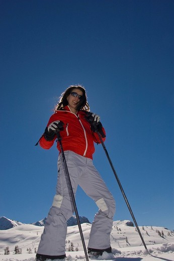 Stock Photo: 1848R-387849 Young woman skiing, posing in front of a blue-sky and mountain landscape
