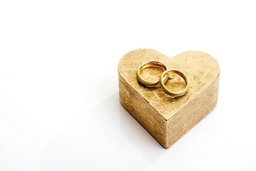 Wedding rings, bands on a heart-shaped golden cardboard gift box : Stock Photo