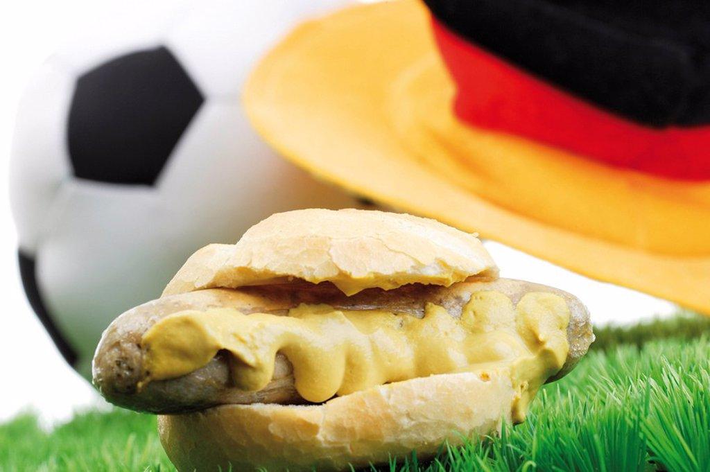 Football fast food - bratwurst dog with mustard, football and German football hat on soccer turf : Stock Photo