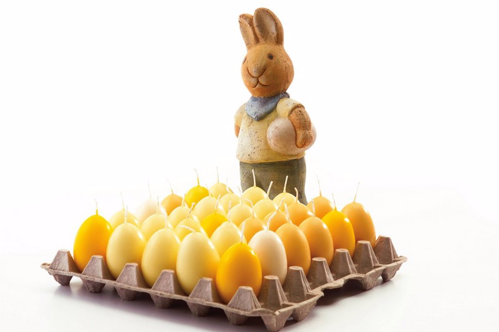 Easter bunny behind a tray of egg-shaped Easter candles : Stock Photo