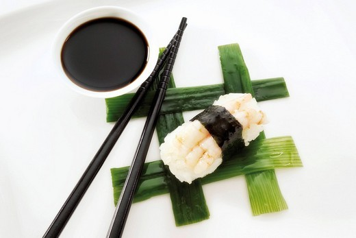 Sushi Nigiri, made with shrimp and rice wrapped in nori seaweed and placed beside black chopsticks and a bowl of soy sauce on interwoven leek strips : Stock Photo